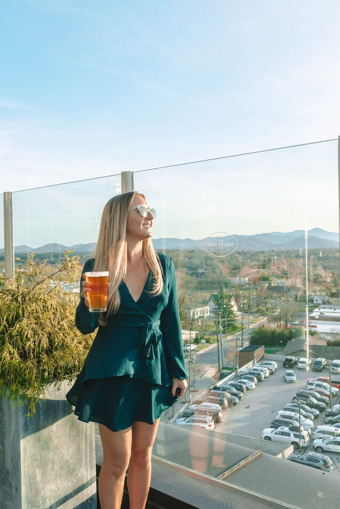 A woman enjoying a beer at The Montford Rooftop Bar during a weekend in Asheville.