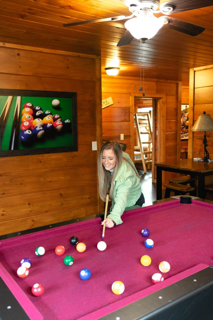 A woman playing pool at Yourcation Awaits in Pigeon Forge, TN