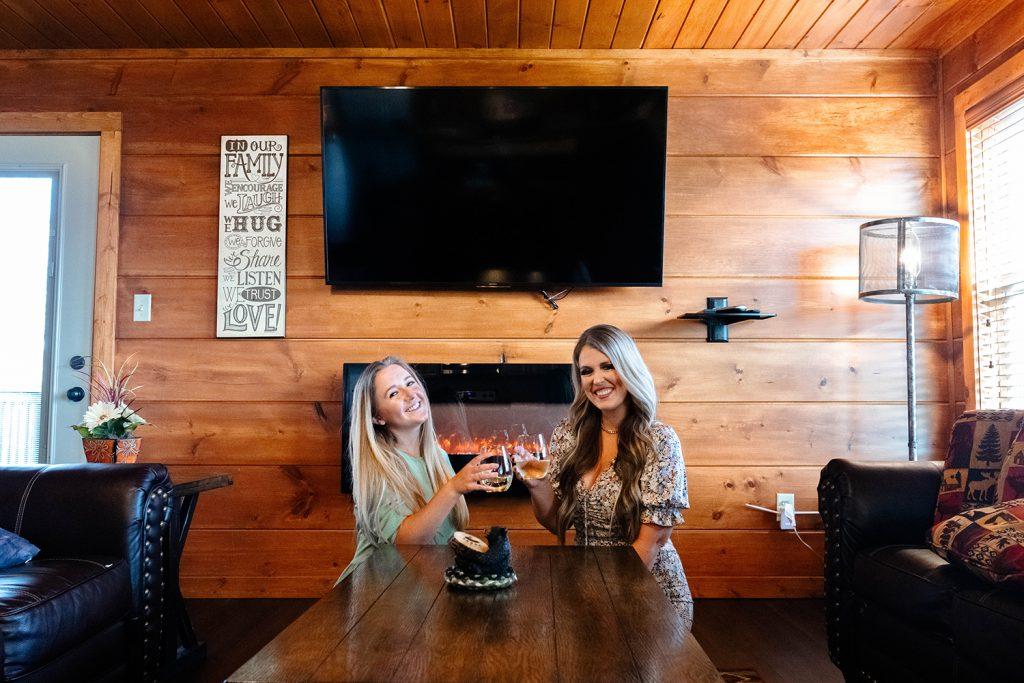 Two women enjoying wine at their cabin rental
