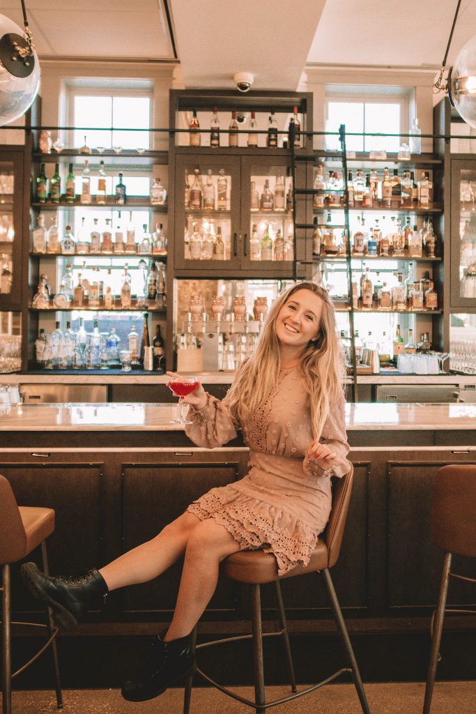 A woman enjoying a cocktail at Elm & Good during a one day adventure in Dallas