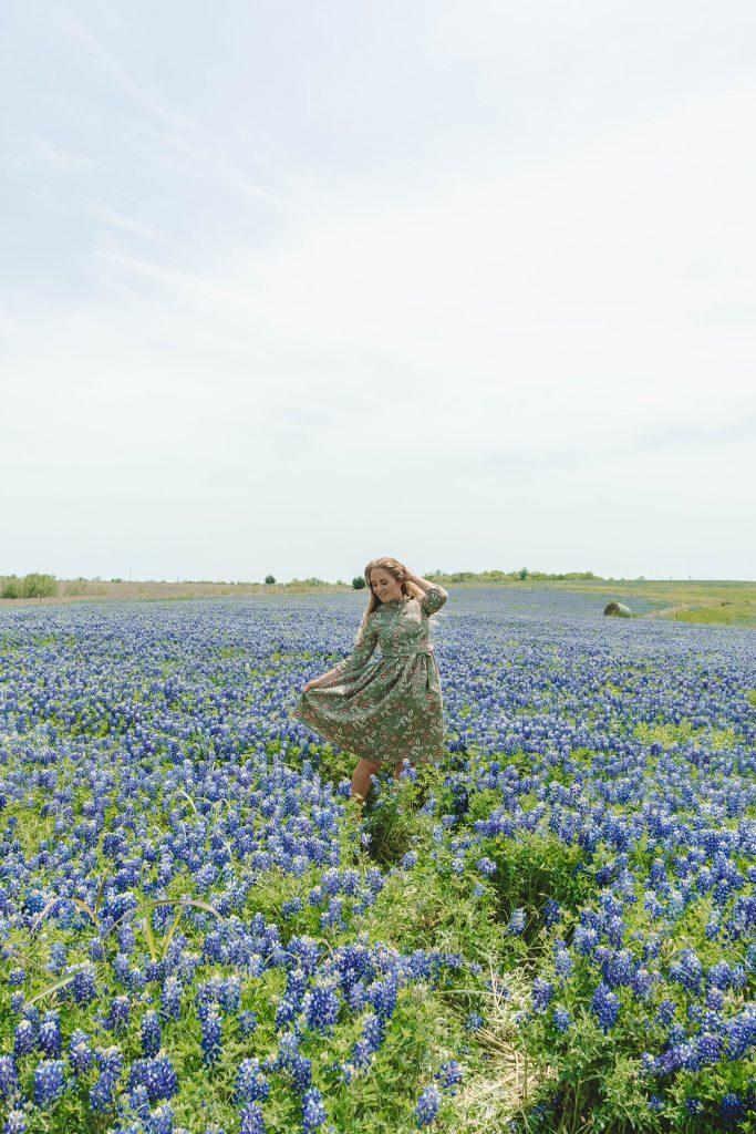 A woman enjoying the Texas bluebonnets in Ennis