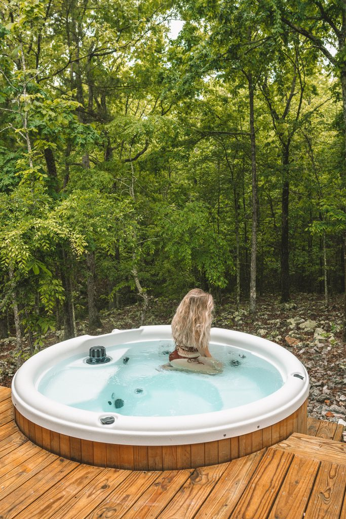 A woman relaxing in a hot tub in the woods of Broken Bow, Oklahoma
