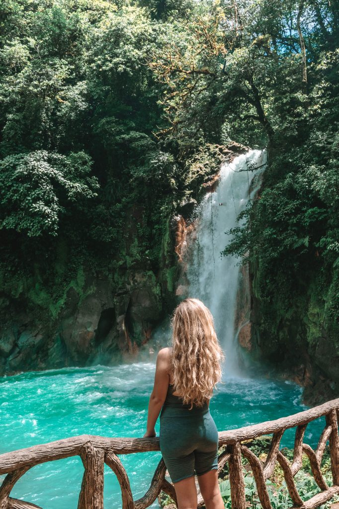 A woman admiring Rio Celeste on a day trip from La Fortuna and Arenal