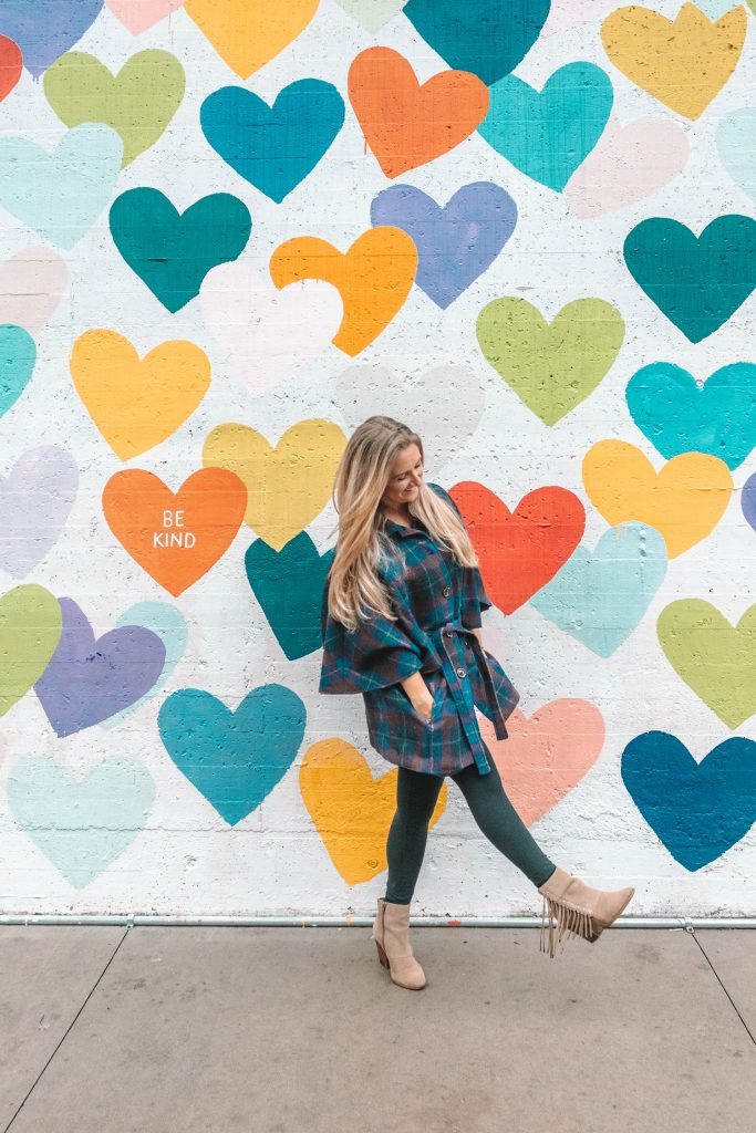 A woman at the Confetti Hearts Wall in Charlotte, North Carolina