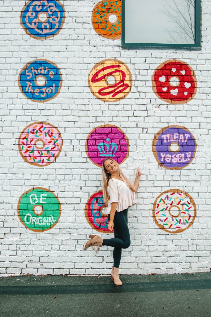 A woman standing in front of the Donut Wall during her one day in Charlotte, NC