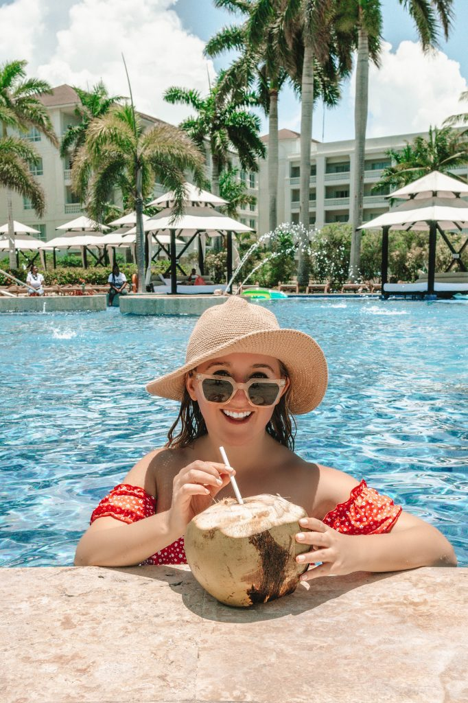 A woman enjoying a coconut at an all inclusive in Jamaica
