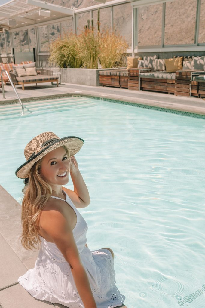 A woman sitting poolside and enjoying a girls' trip to Palm Springs