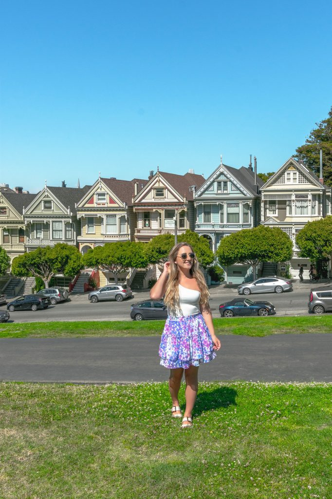 A woman in front of the Painted Ladies in San Francisco