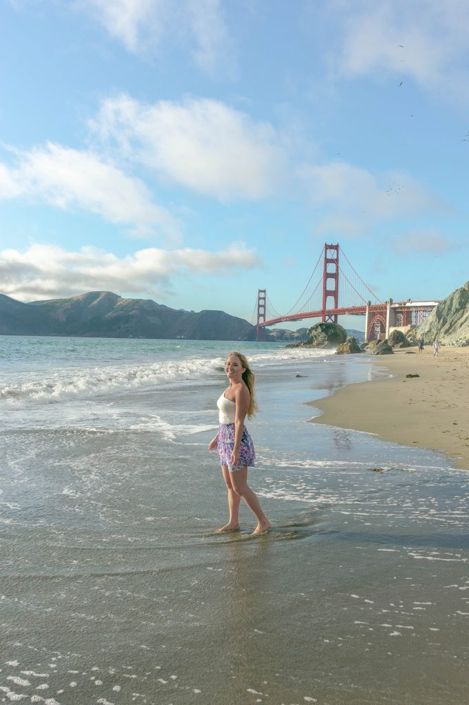 A happy woman at Marshall's Beach with the Golden Gate Bridge in the background