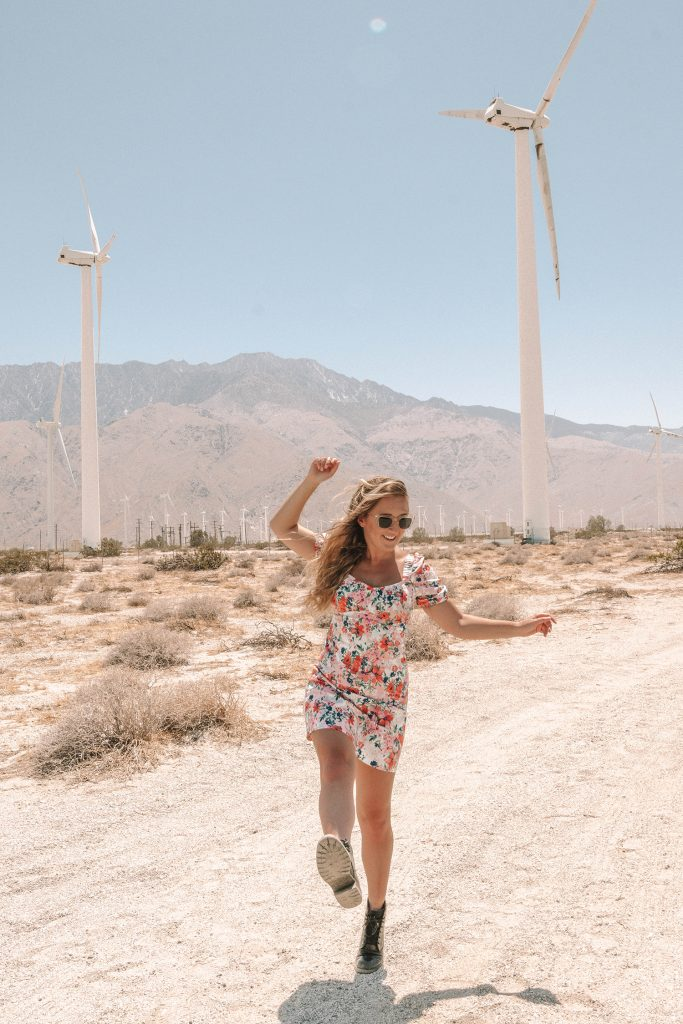 A woman having fun at the windmill location on a girls' trip to Palm Springs