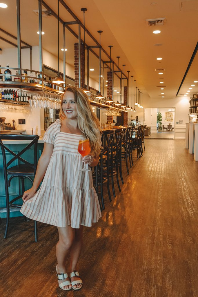 A woman enjoying an Aperol Spritz during dinner at Carboni's Ristorante on a California Wine Country road trip