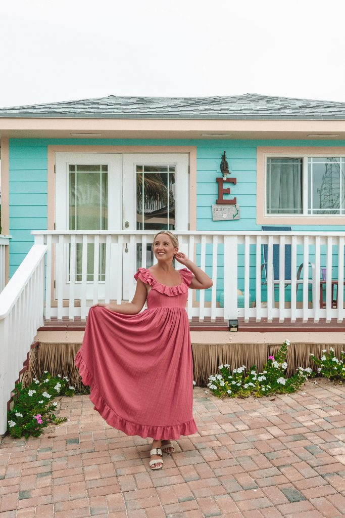 A woman standing in front of a colorful villa at Embrace Resort