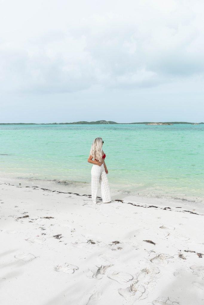 A woman walking on Palm Bay Beach on Great Exuma Island
