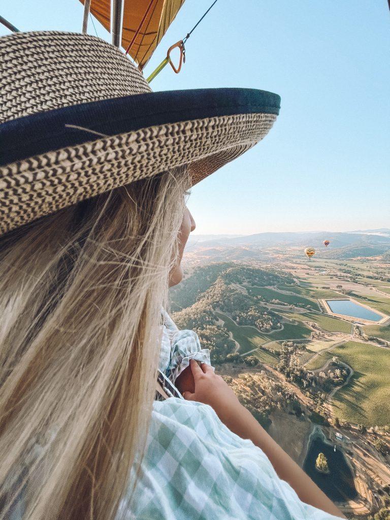 A woman enjoying the views on a hot air balloon ride over Napa Valley.