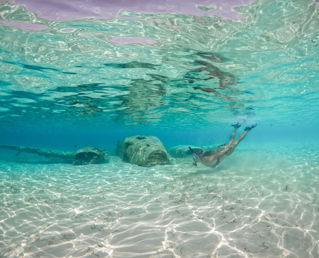 A woman snorkeling at a plane wreck in Staniel Cay, Exuma, Bahamas