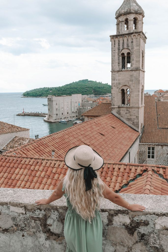 A woman walking the city walls of Dubrovnik, what you must add to your bucket list