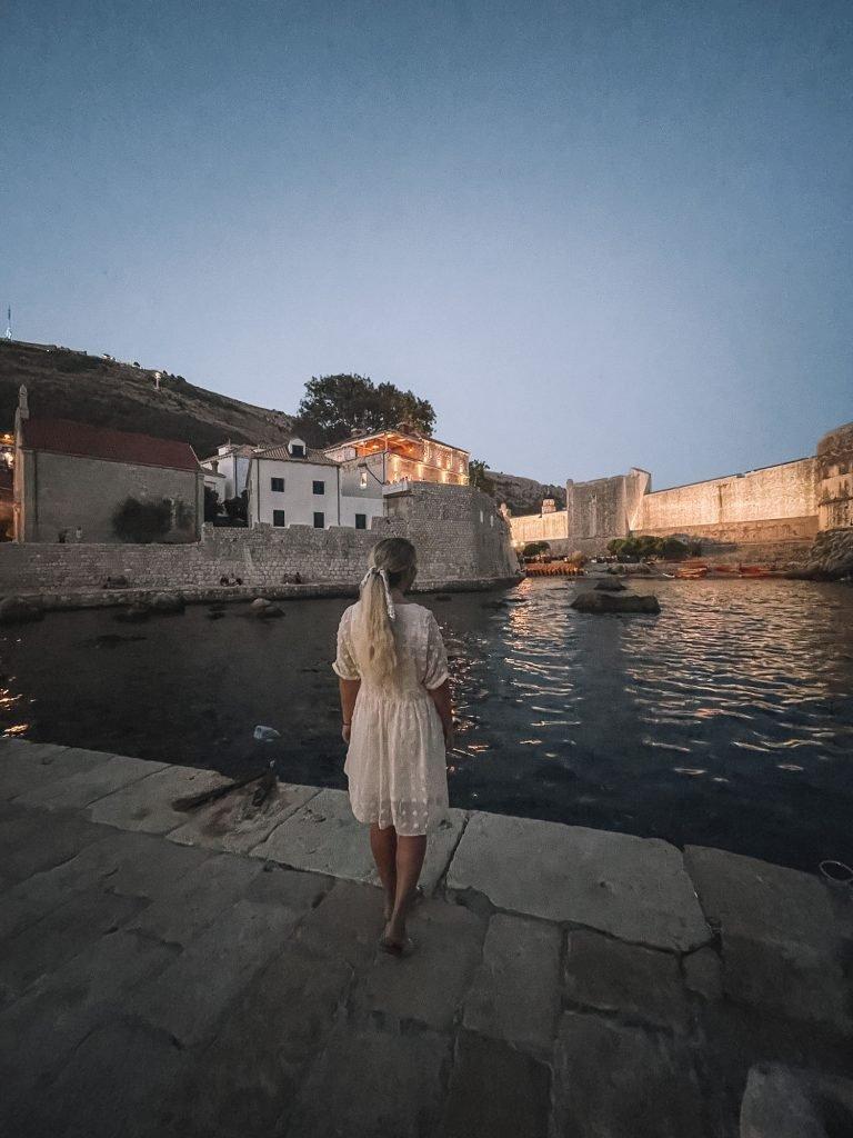 A woman enjoying Dubrovnik at night.
