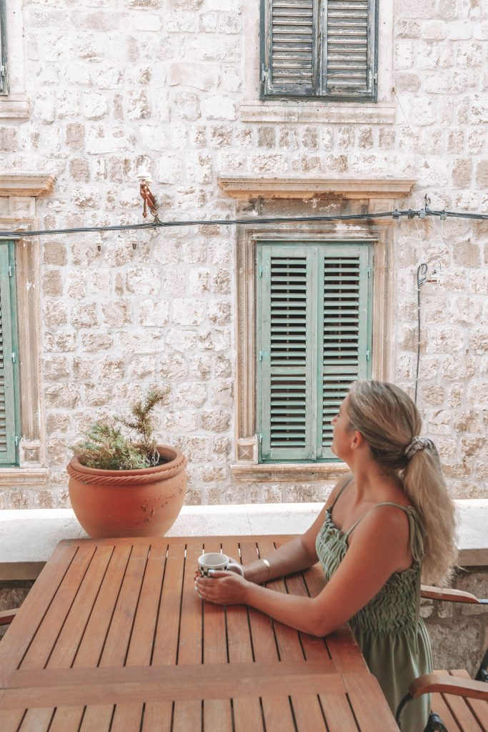 A woman sipping coffee at The Pucic Palace