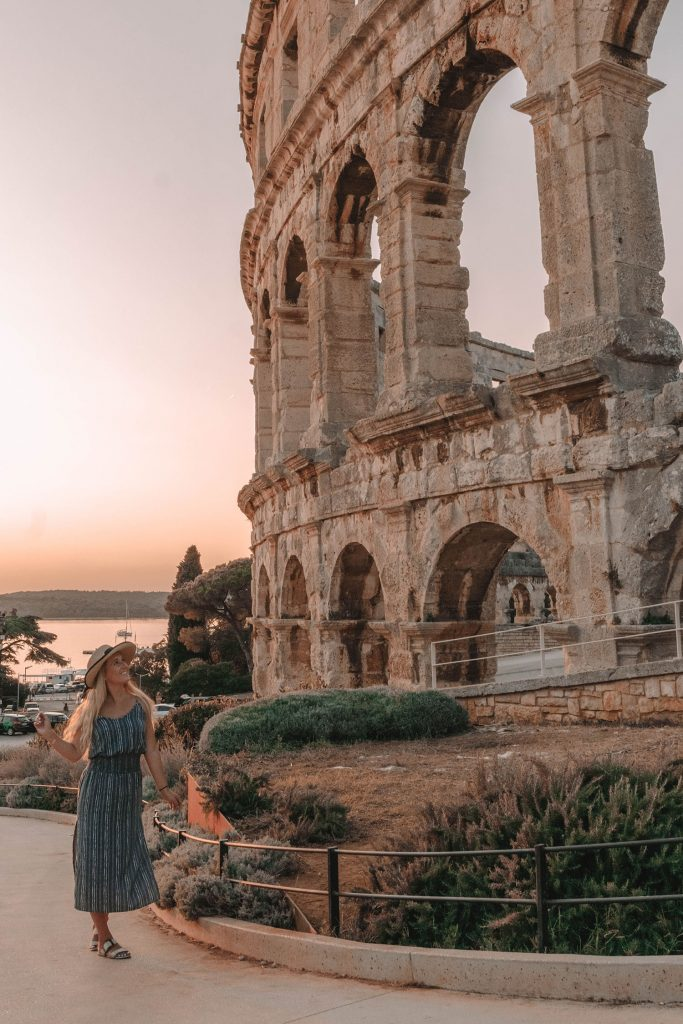 A woman at Pula Arena during sunset in Istria